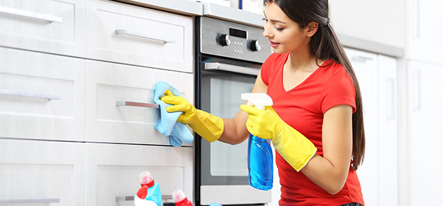 Woman maid cleans outside of kitchen cabinet for a move in cleaning